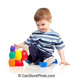 Funny little child is playing with color toys, isolated over white