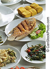 Indonesian fried fish menu served with vegetables, rice,...