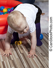 Baby taking first steps - Young baby girl balanced on her...