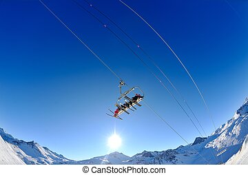 Ski lift - happy skiers use vertical transport on ski...