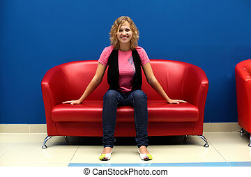 Young woman sitting on red sofa - Portrait of young woman...