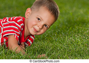 Little boy in red on the green grass - A cheerful little boy...