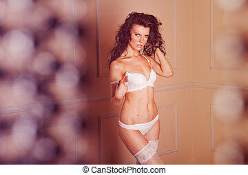 Beautiful and sexy brunette girl wearing white lingerie