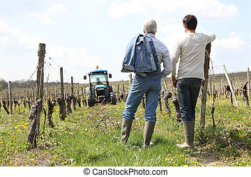 Two men stood in vineyard