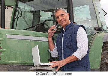 farmer near a tractor with computer