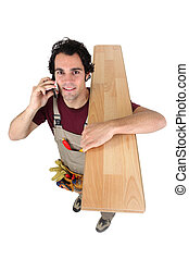 Worker on the phone while carrying wooden flooring