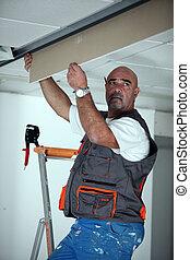 Manual worker repairing ceiling panel