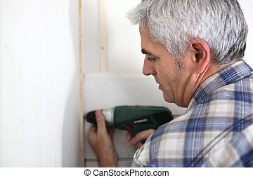 Grey haired handyman drilling into wall