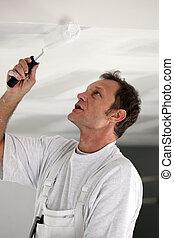 Painter repainting ceiling
