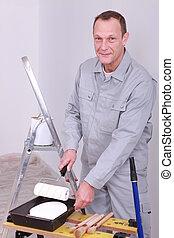 Decorator preparing paint roller