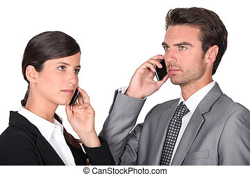 Business man and woman using cellphones
