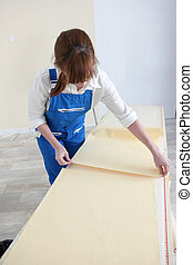 Woman laying out sheets of wallpaper
