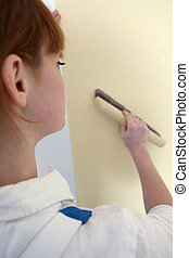 Woman passing brush over wall paper