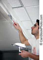 Man applying plaster to a ceiling