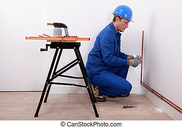 Plumber fitting new pipes to wall