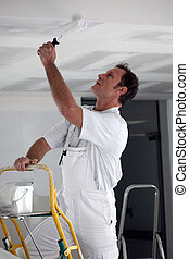 Painter using roller to coat ceiling