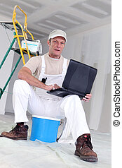 Painter with laptop sat with ladder