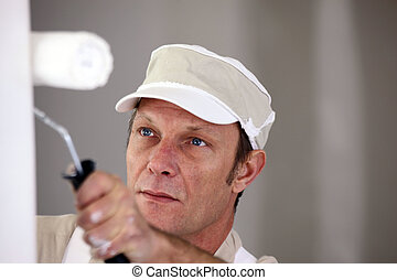 Man using paint roller on wall