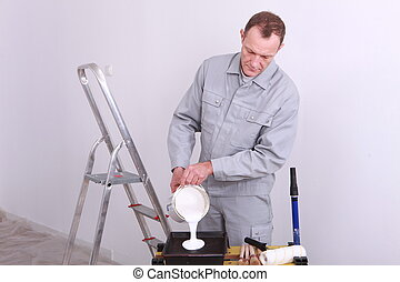 Decorator pouring paint into a tray