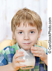 boy with milk mustache after drinking from glass