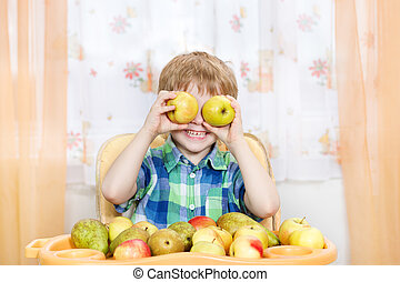 Happy boy playing with apples in front of the table with fruits. Indoors portrait