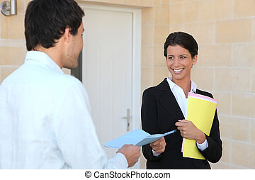 Agent with a client outside a front door