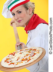 Woman putting pizza in oven