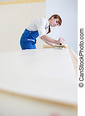 Woman pasting wallpaper