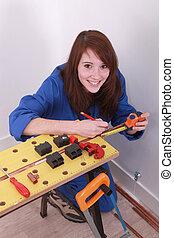 Woman measuring a copper pipe
