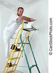 Painter climbing ladder to paint ceiling