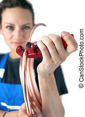 Tradeswoman inserting a copper tube into a clamp