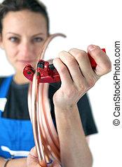Tradeswoman inserting a copper tube into a clamp
