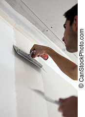 Worker plastering a wall