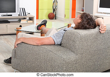 Young man at home on his sofa