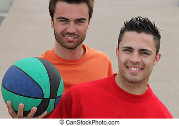 Two men playing basketball outdoors