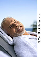 Grey-haired man on sun lounger