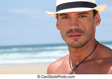 Man with hat on the beach