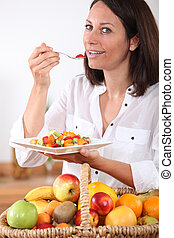 Health conscious brunette eating fruit salad
