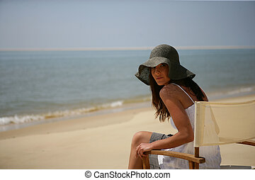 Woman sitting on a chair on the beach