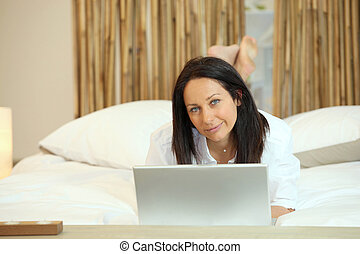 Woman lying in bed with computer