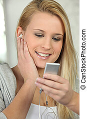 Blonde teen listening to music