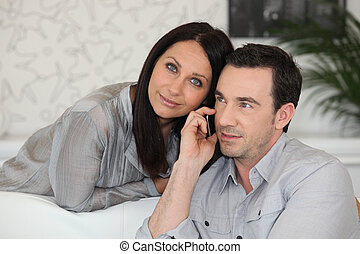 Couple with a phone at home