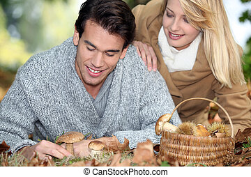 Couple with basket full of mushrooms and chestnuts