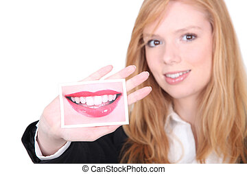 Woman with picture of large smile in hand