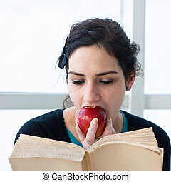Portrait of a pretty young student eating an apple while...