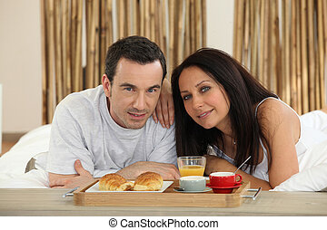 Couple with breakfast served on a tray