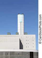 Incineration plant with chimney against blue sky