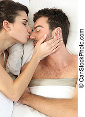 Couple kissing in bed