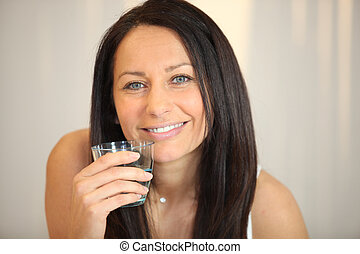 Brunette woman with glass of water