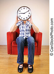 Woman holding a clock covering her face - Woman sitting in a...